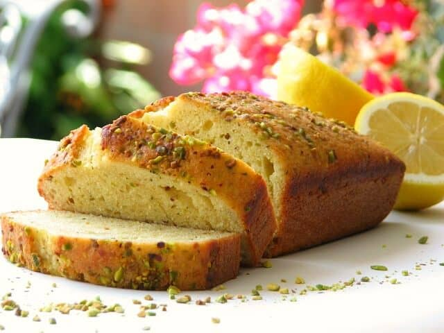 Slices of lemon loaf cake topped with crunchy pistachios
