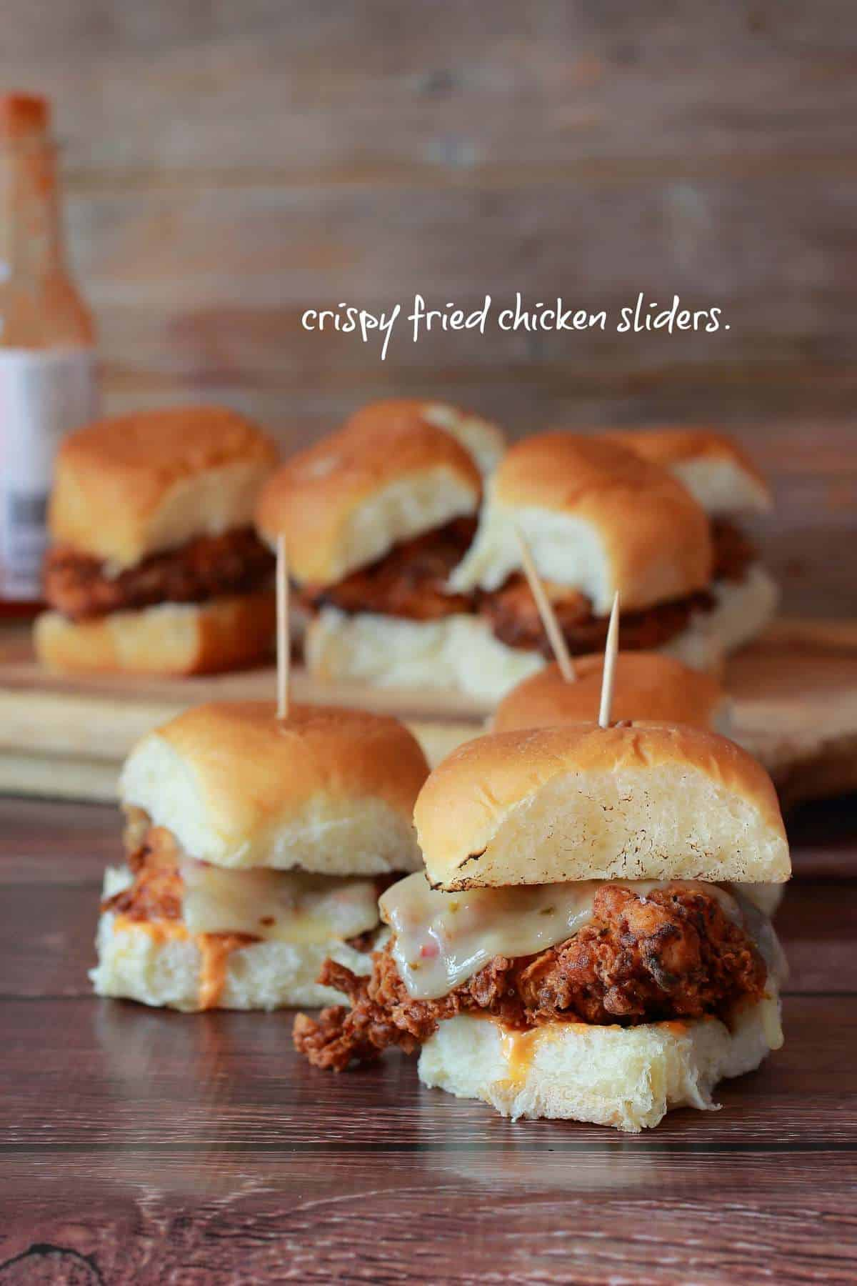 Crispy Fried Chicken sliders with melted cheese and buffalo sauce!
