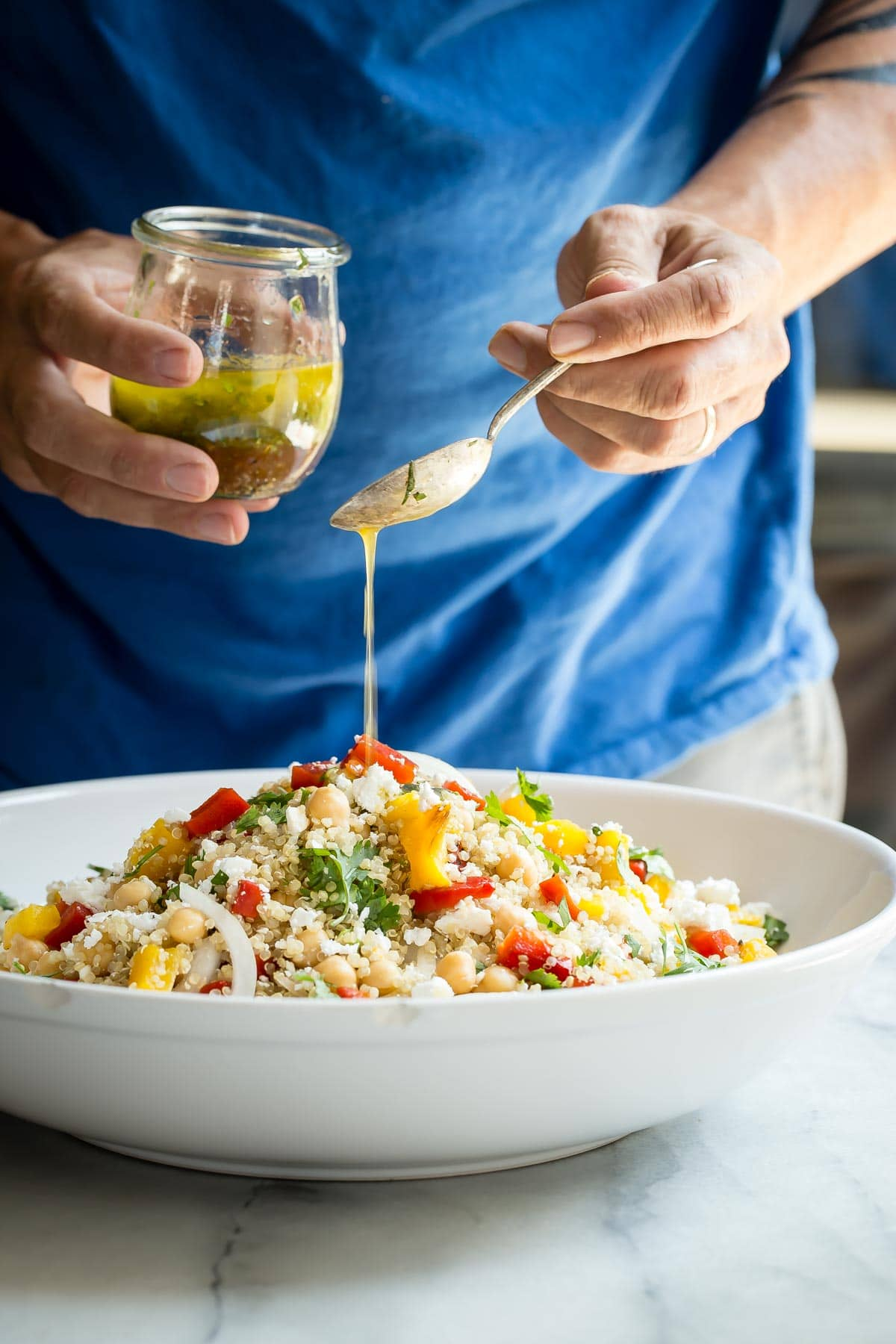 Pouring olive oil herb dressing over my healthy quinoa salad