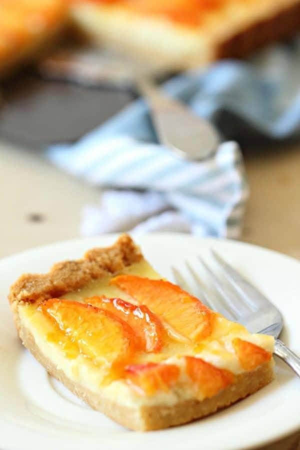 Slice of homemade peach custard tart in a buttery crust