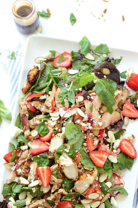 Chunks of grilled balsamic chicken salad are tossed with strawberries and feta cheese