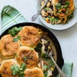 A bowl of chicken pot pie southwestern style with cilantro, black beans, corn and peppers