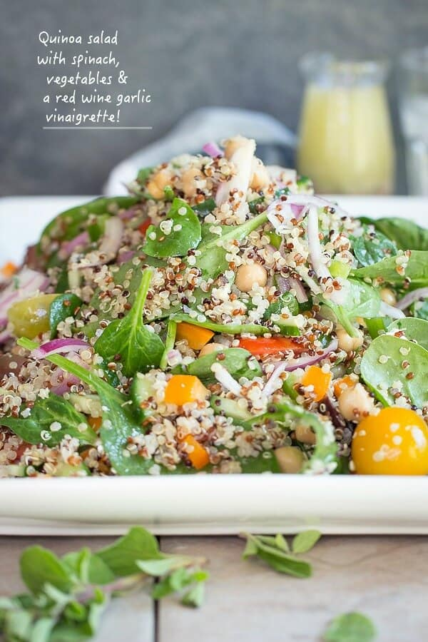 A quinoa power salad full of spinach, garbanzo beans, onion and tomatoes