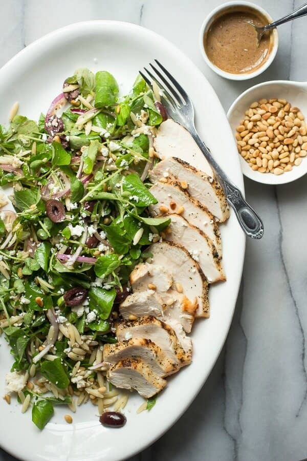A healthy watercress salad with pine nuts, olives, cheese and grilled chicken