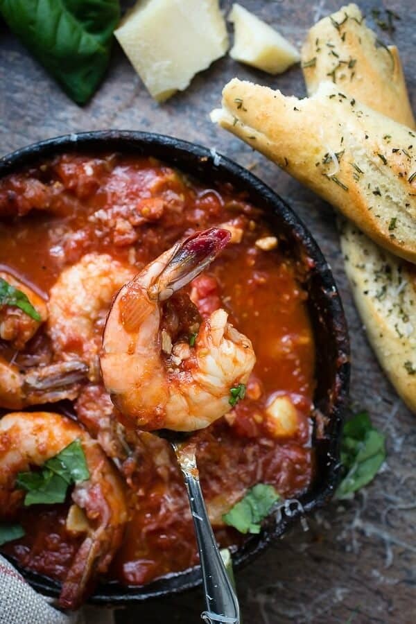 Roasted garlic cloves in a tomato sauce with giant shrimp
