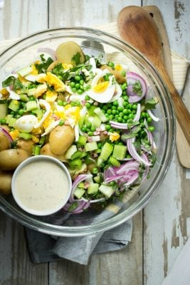Potato salad with eggs, pancetta and peas
