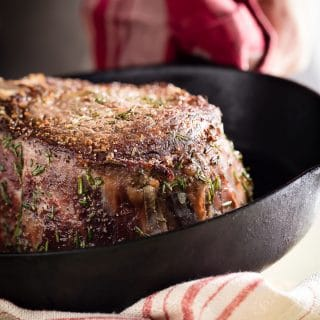 The biggest juiciest ribeye steak covered in fresh rosemary, sea salt and cracked black pepper