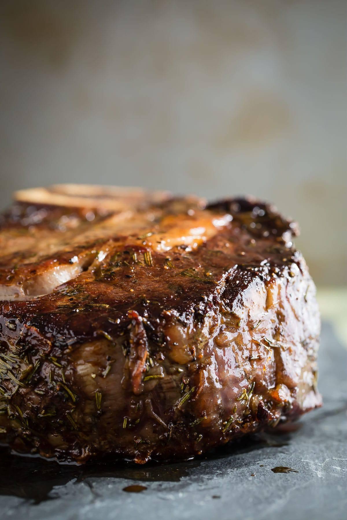 The biggest juiciest ribeye steak covered in fresh rosemary, sea salt and cracked black pepper