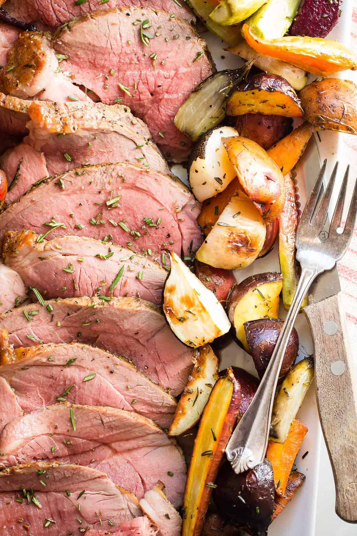 Juicy roast leg of lamb served with roasted root vegetables