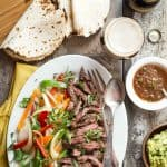 Juicy Negra Modelo marinated steak fajitas with peppers and onions . Serve on warm charred tortillas with guacamole and salsa.