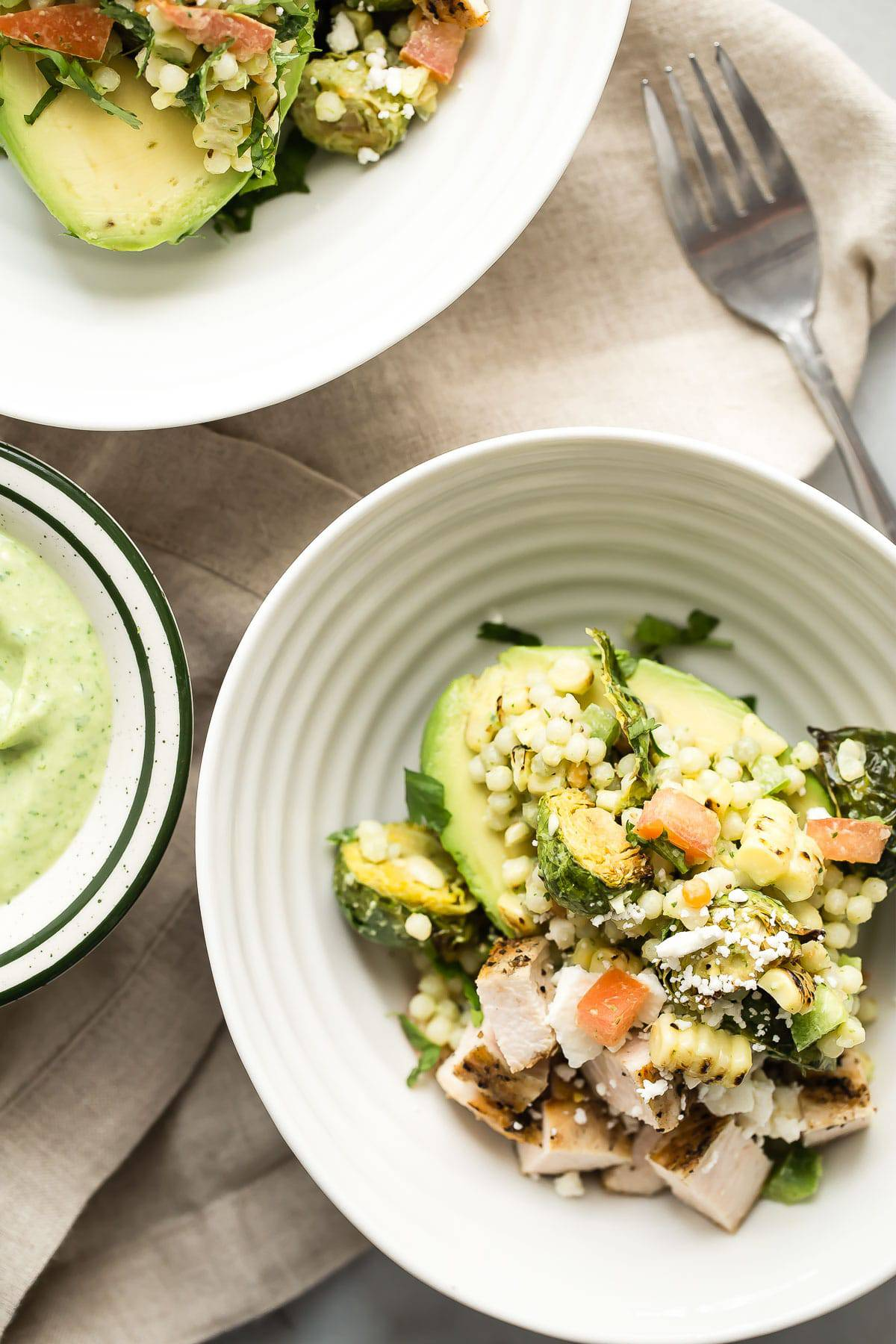 Avocado feta bowl topped with couscous, grilled chicken and charred corn, the perfect healthy lunch.
