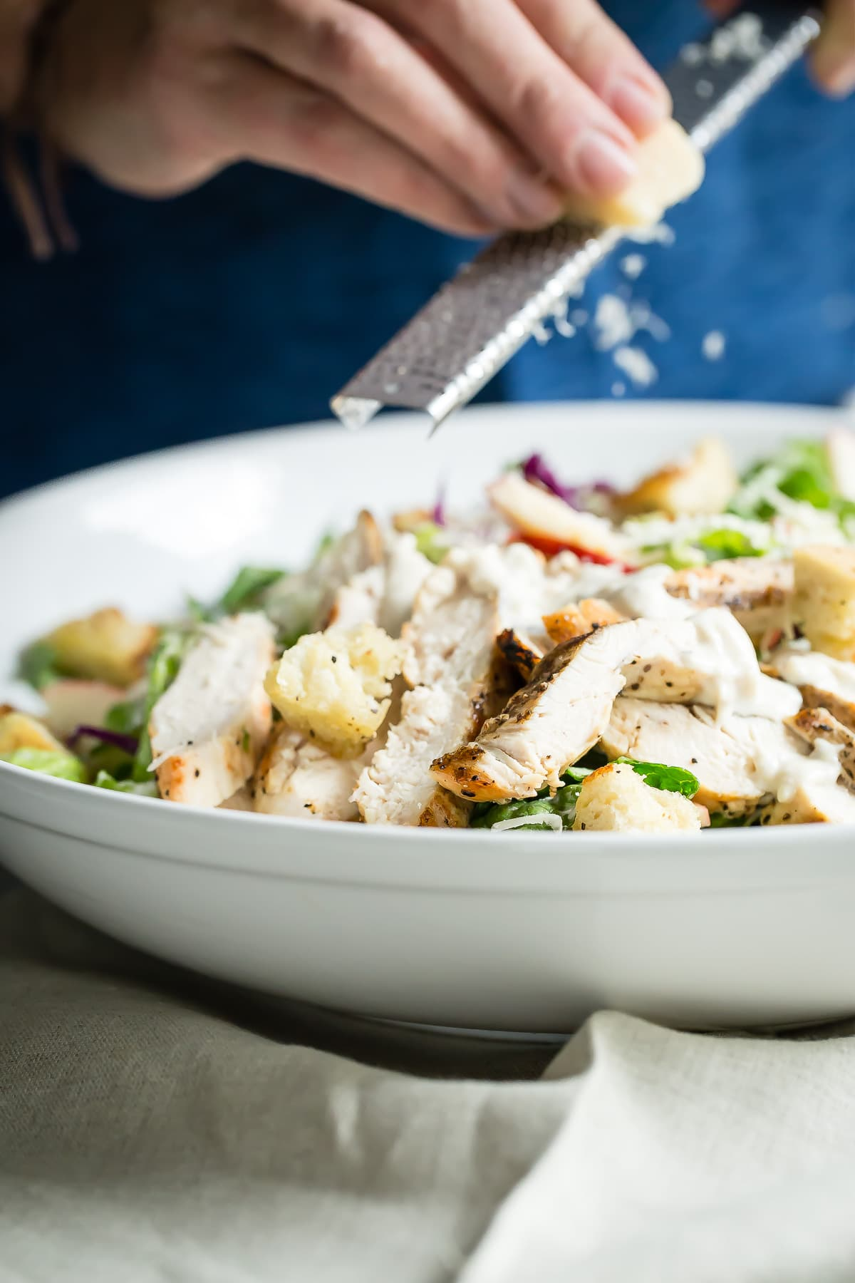 Chunks of grilled chicken, apple, and red cabbage are tossed with a homemade Caesar Salad dressing