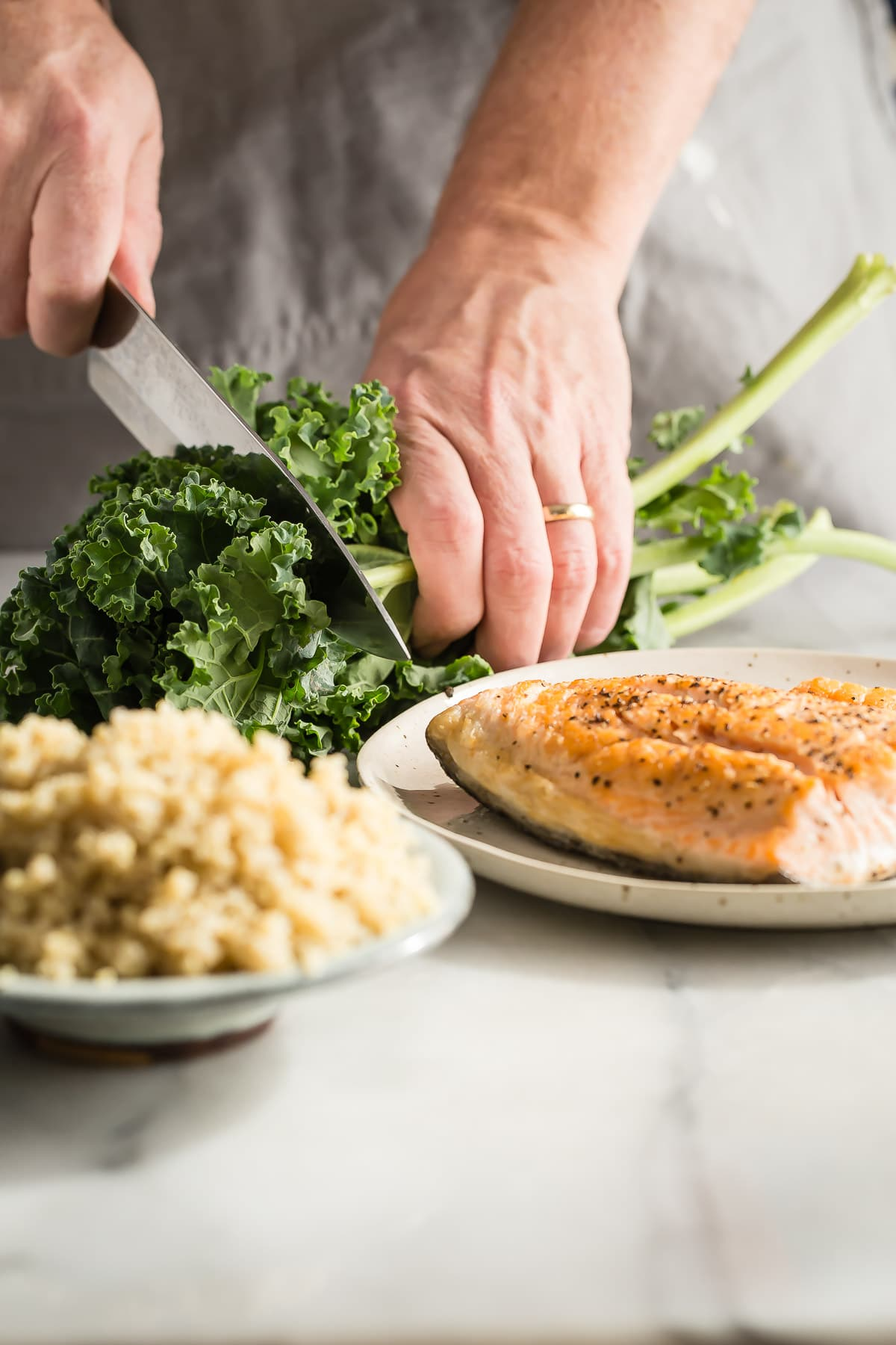 Roasted salmon flakes with quinoa and fresh steamed kale. This healthy kale salad is dressed in a tangy garlic and lemon sauce.