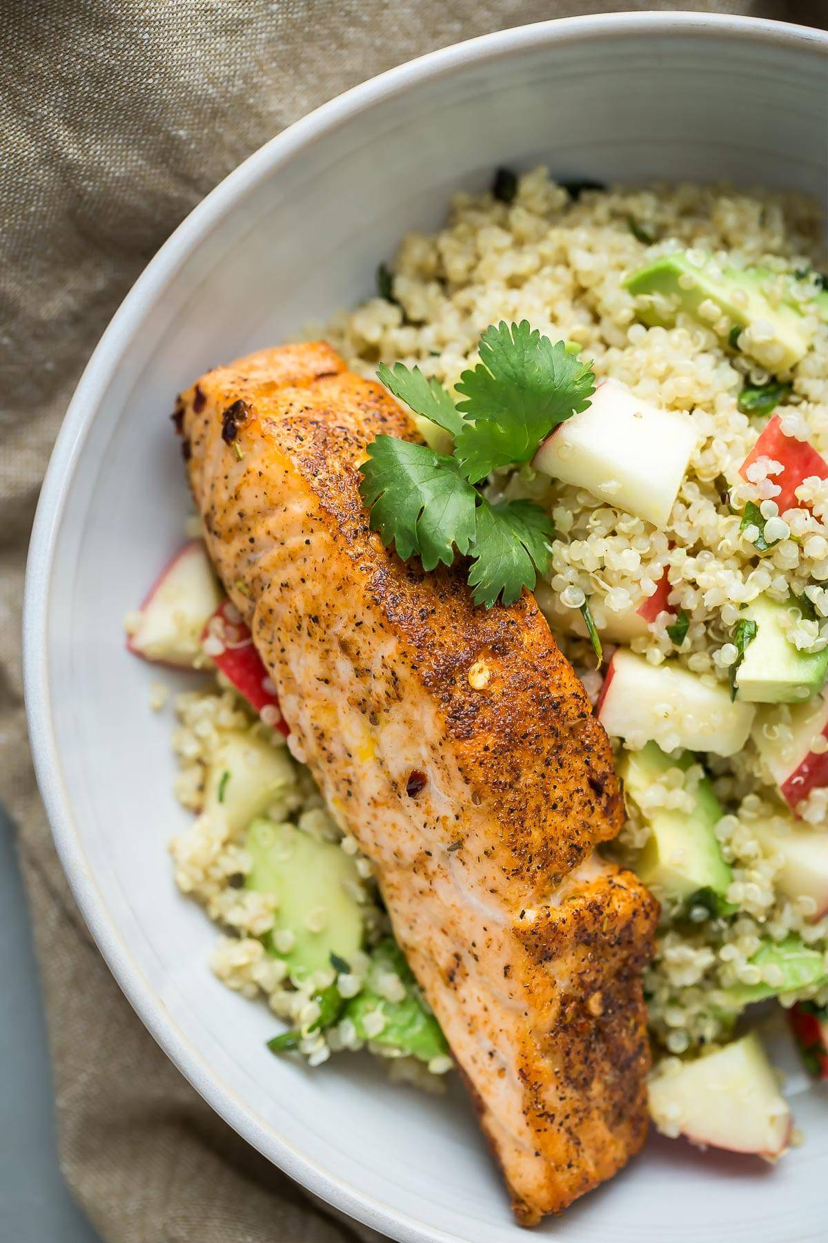 Healthy salmon with quinoa, apples and avocado, dressed with a fresh herb vinaigrette.