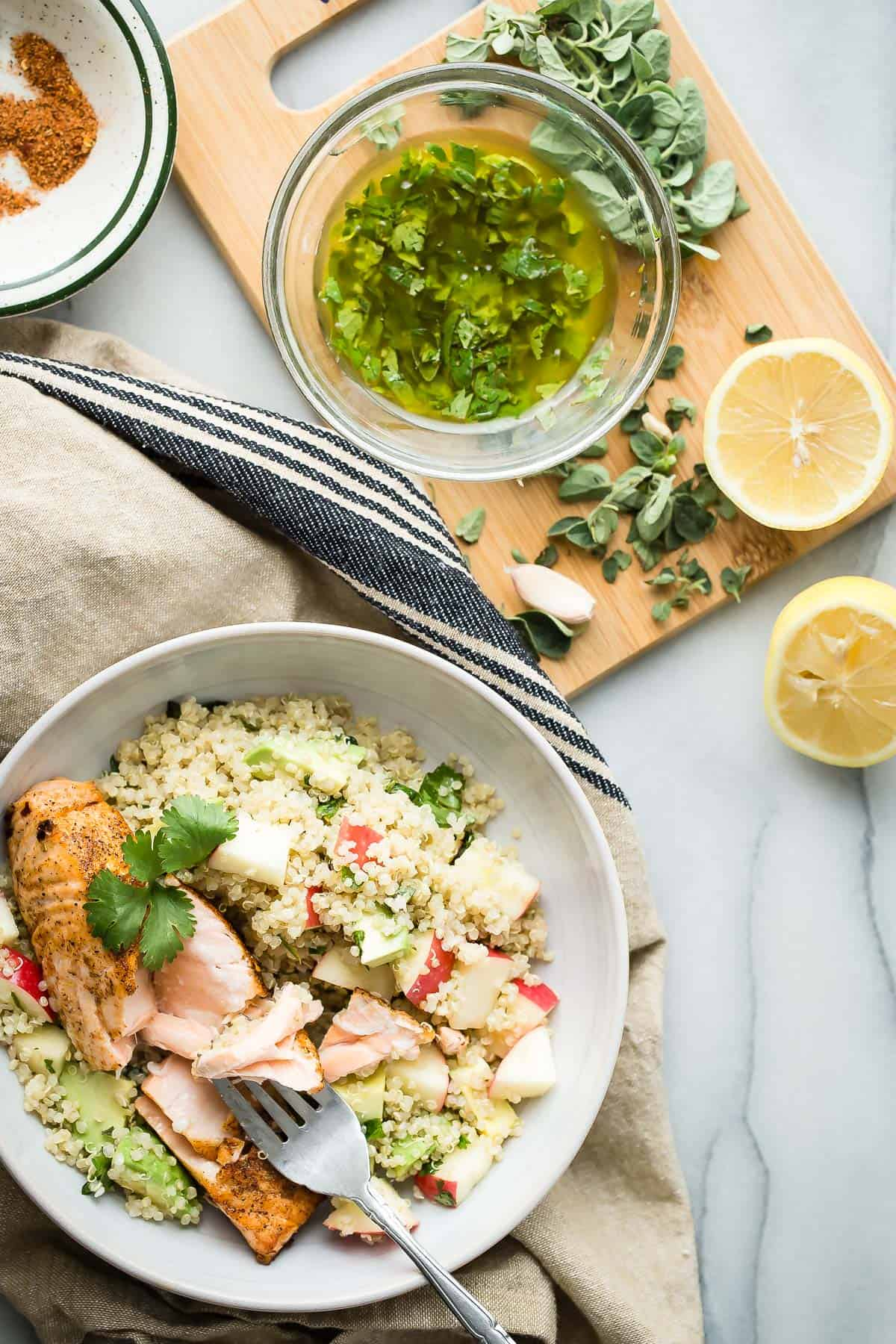 Healthy salmon quinoa bowl with apples, avocado and dressed with a fresh herb vinaigrette.