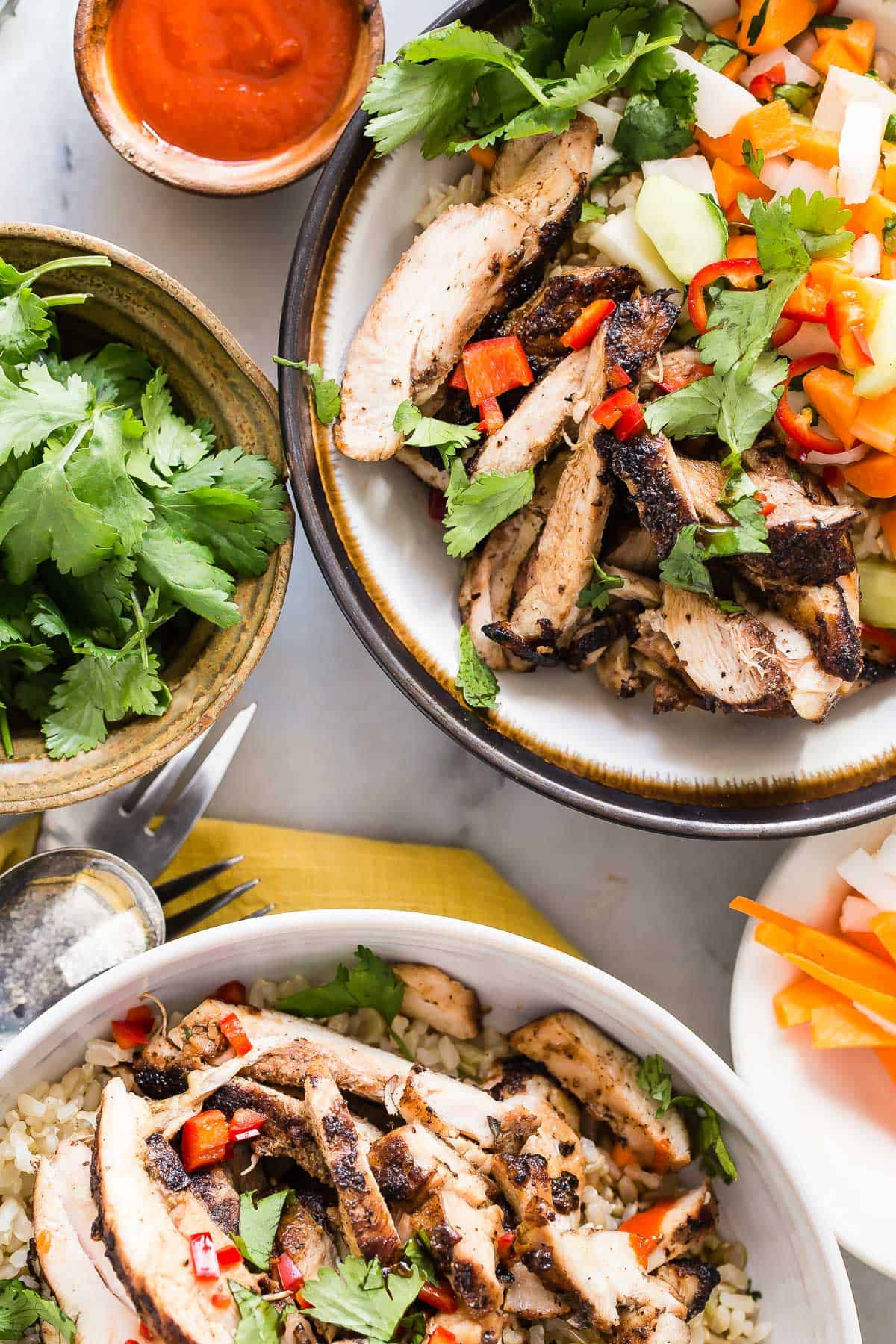 Chicken rice bowl topped with five spice chicken, pickled daikon and carrots