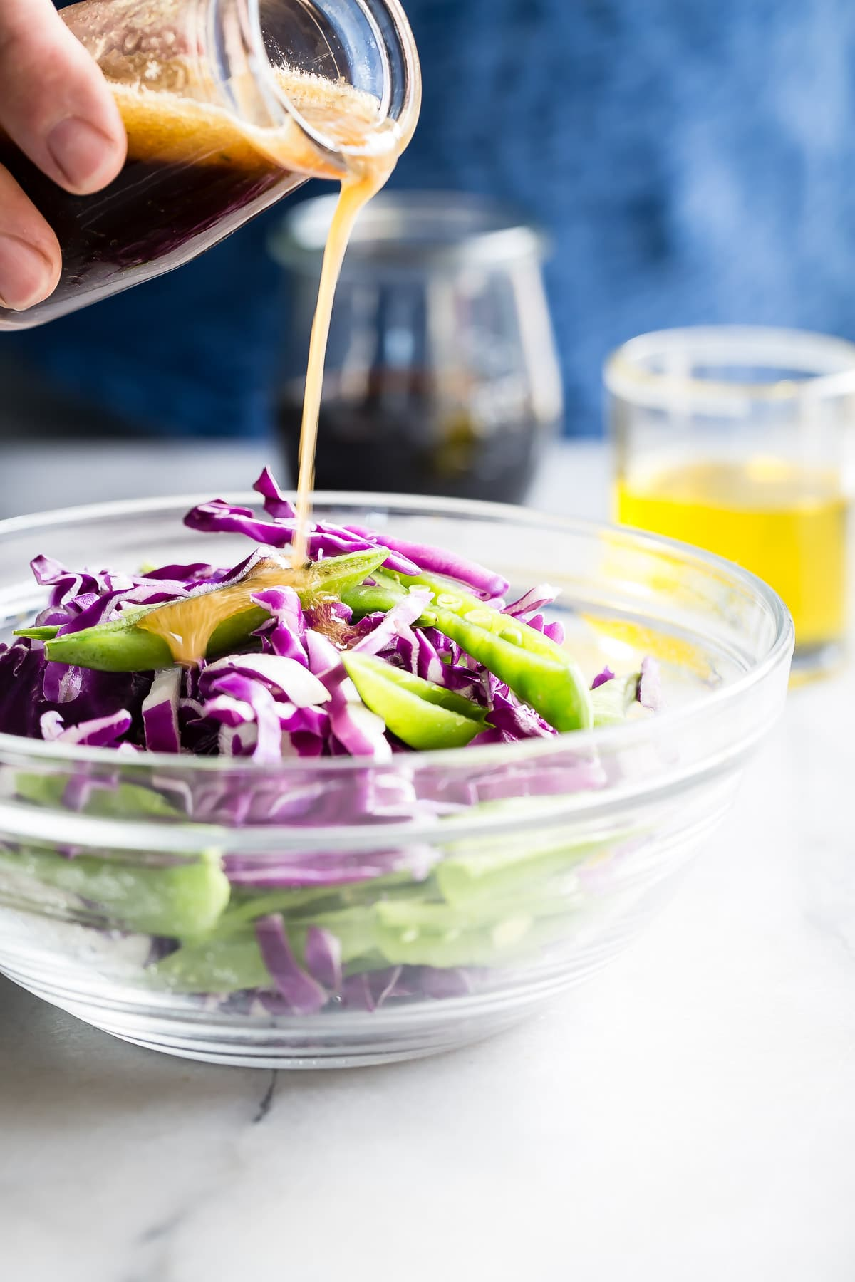 Pouring salad dressing onto coleslaw
