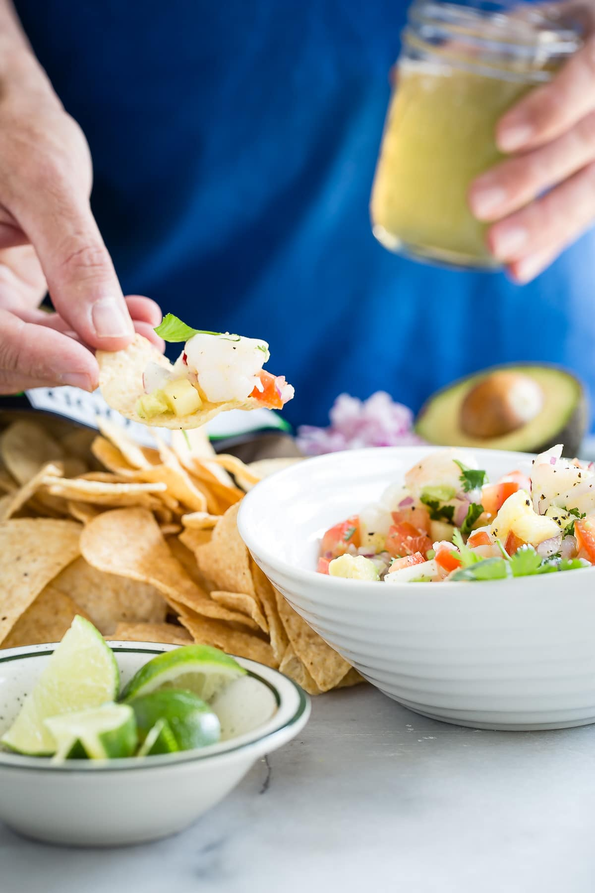 Dipping chips into a bowl of ceviche