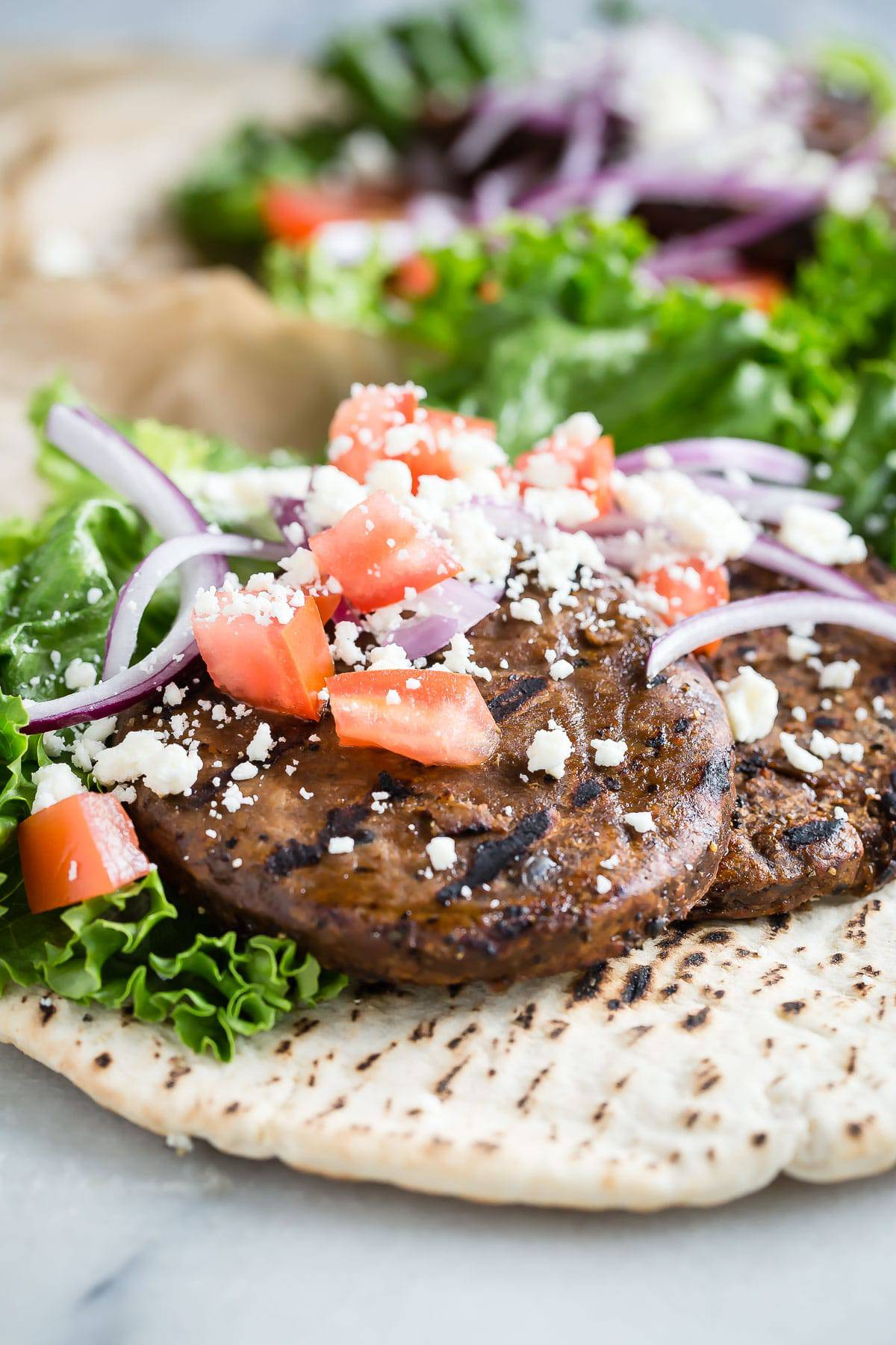 An easy and filling pita sandwich stuffed with two grilled black bean patties, lettuce, tomato, red onion and feta cheese. Skip the bun and go for less calories with pita!