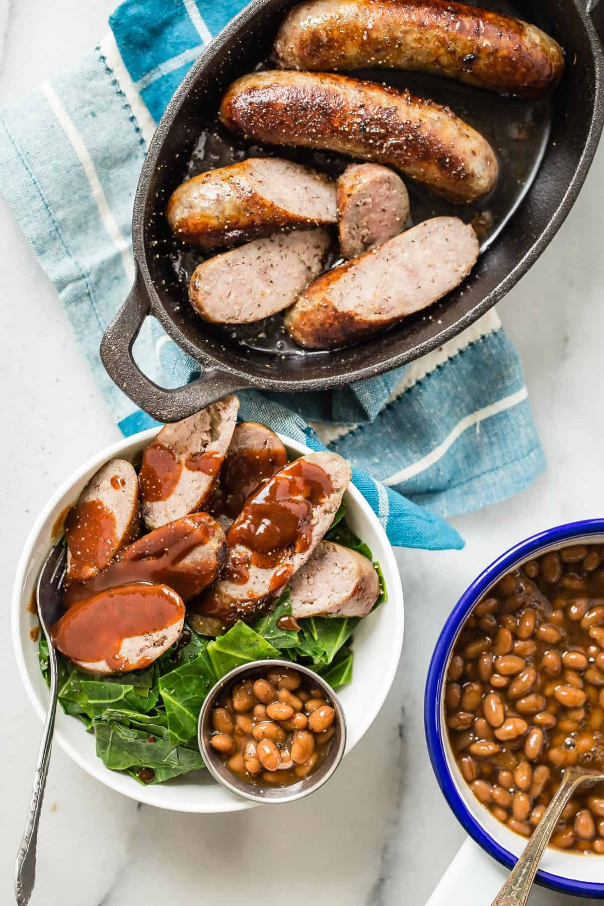 Bratwurst sausages with southern style collard greens, baked beans and a smoky barbecue sauce on top. This is the perfect way to enjoy some juicy brats and celebrate Bratsgiving!