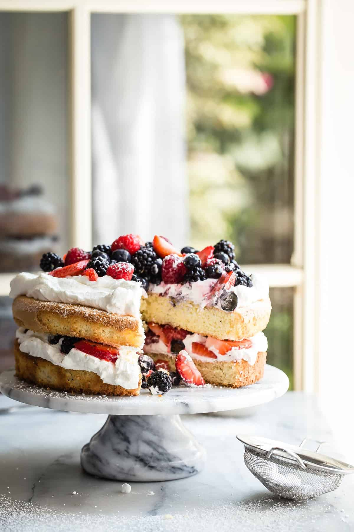 This light and fluffy mixed Berry and Cream Sponge Cake is layered with jam, heavy whipping cream and fresh berries. If you need a simple no fuss cake, then this is the recipe.