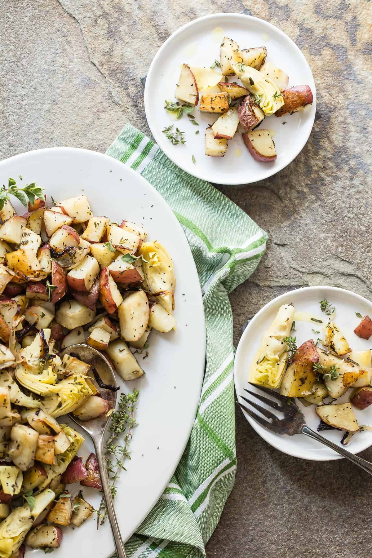 Roasted Red Potatoes with fresh rosemary, thyme and oregano and tossed in olive oil. The final piece of this side dish extravaganza is to add artichoke quarters!