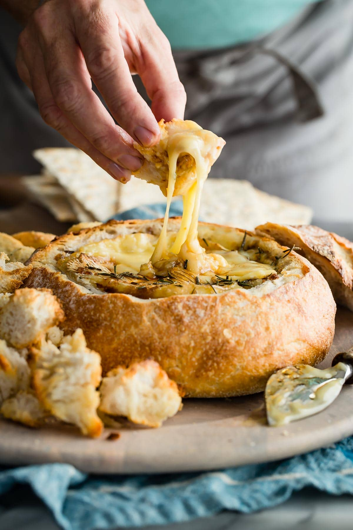 The ultimate holiday party appetizer. Baked Brie in a Sourdough Bread Bowl topped with brown sugar, white wine and fresh rosemary! #bakedbrie #cheese #holidayrecipes