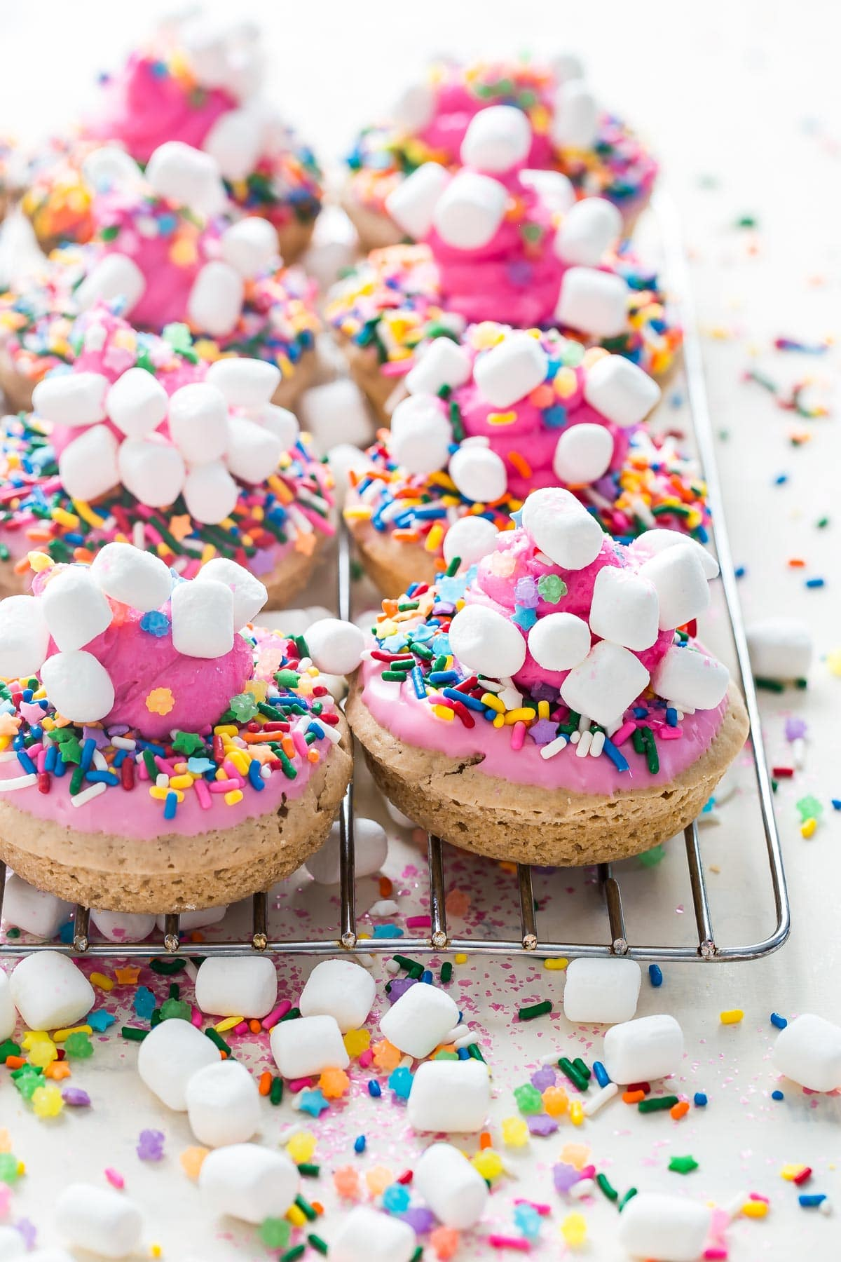 Baked Strawberry Donuts covered in an absurd amount of unicorn sprinkles and mini marshmallows!
