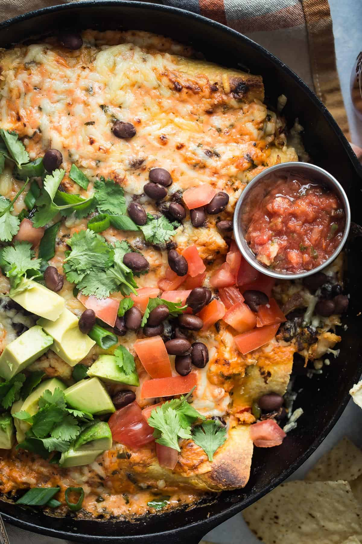 Easy Chicken enchiladas never looked so darn tasty, with beans and so much gooey cheese!