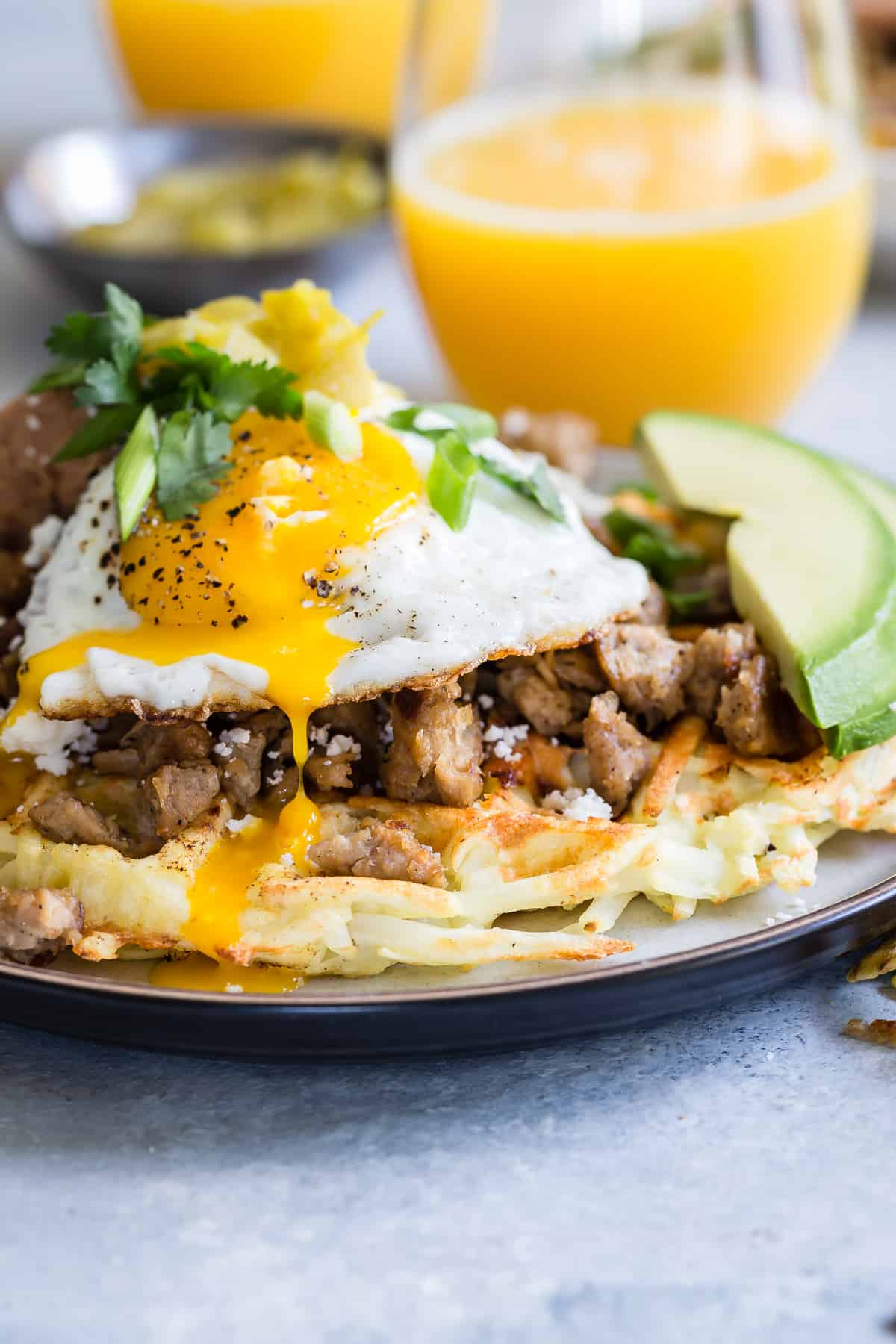 Hash Browns cooked in a waffle press and topped with so many awesome flavors including Lightlife Vegetarian Sausage, beans, chilies and avocado!
