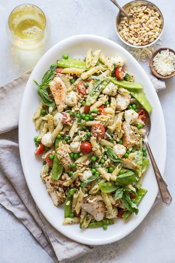 An easy and fresh Pesto Pasta Salad with grilled chicken and peas. Perfect for easy dinners and backyard summer party plans!