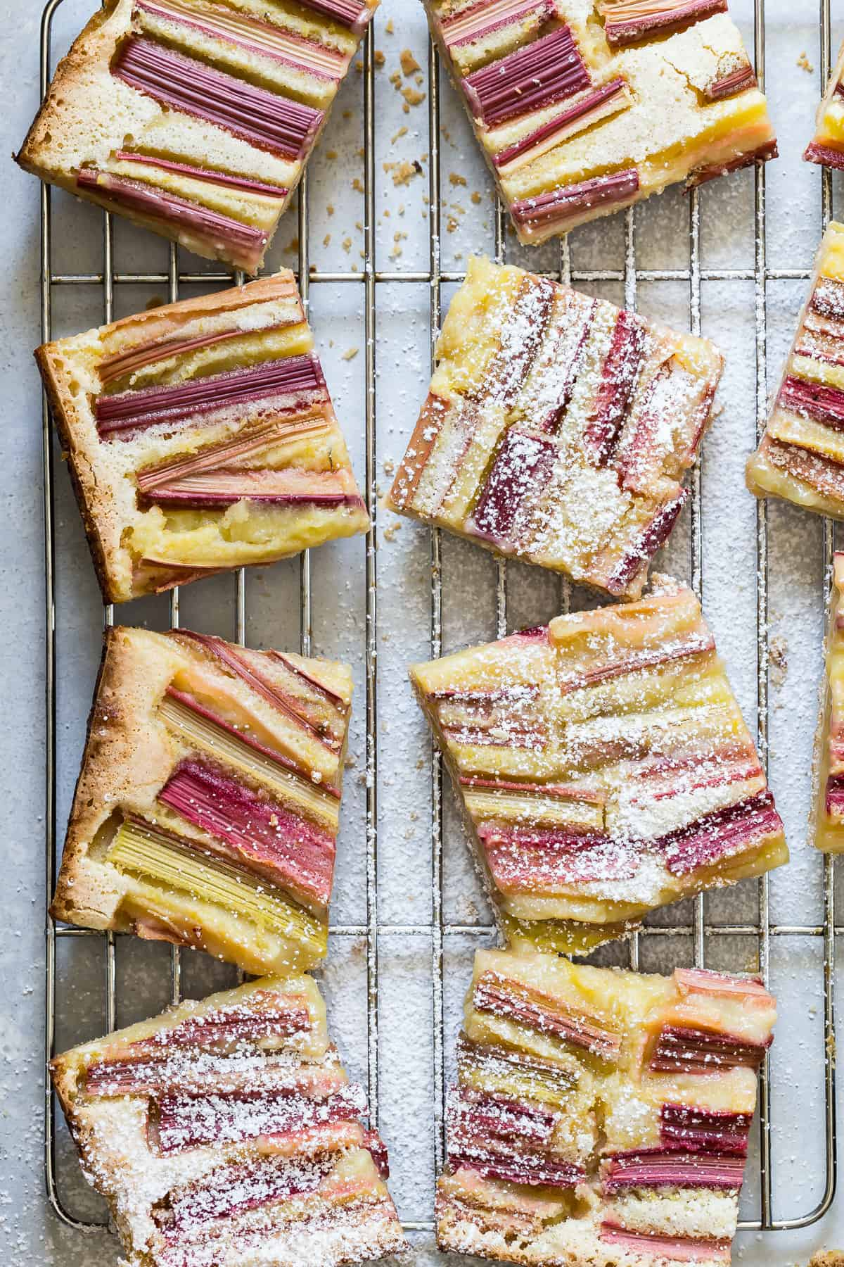 Lemon bars topped with fresh rhubarb and dusted with powdered sugar for an awesome summers dessert!