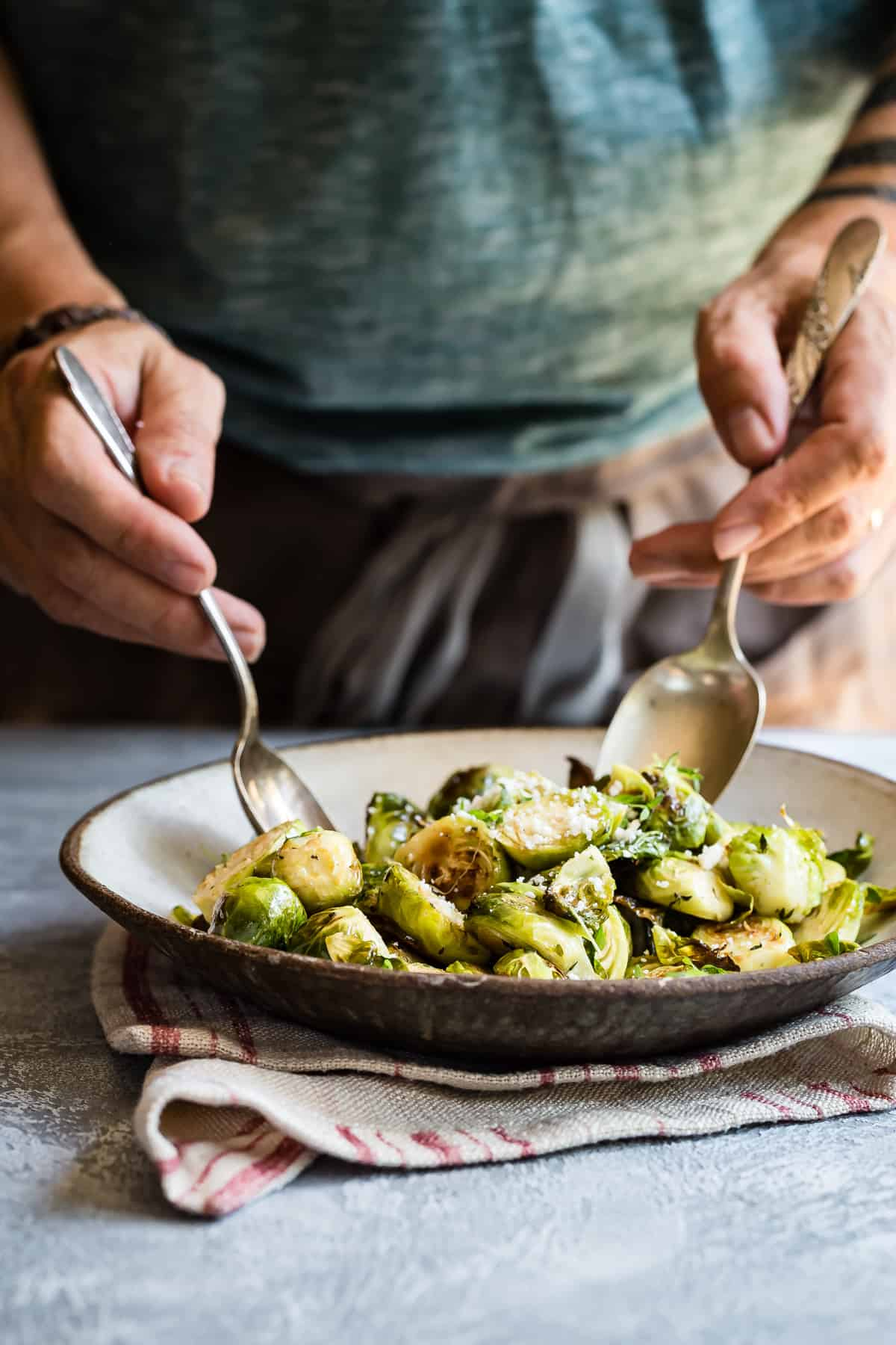 Tossing roasted brussels sprouts in a fresh thyme buttery spread sauce.
