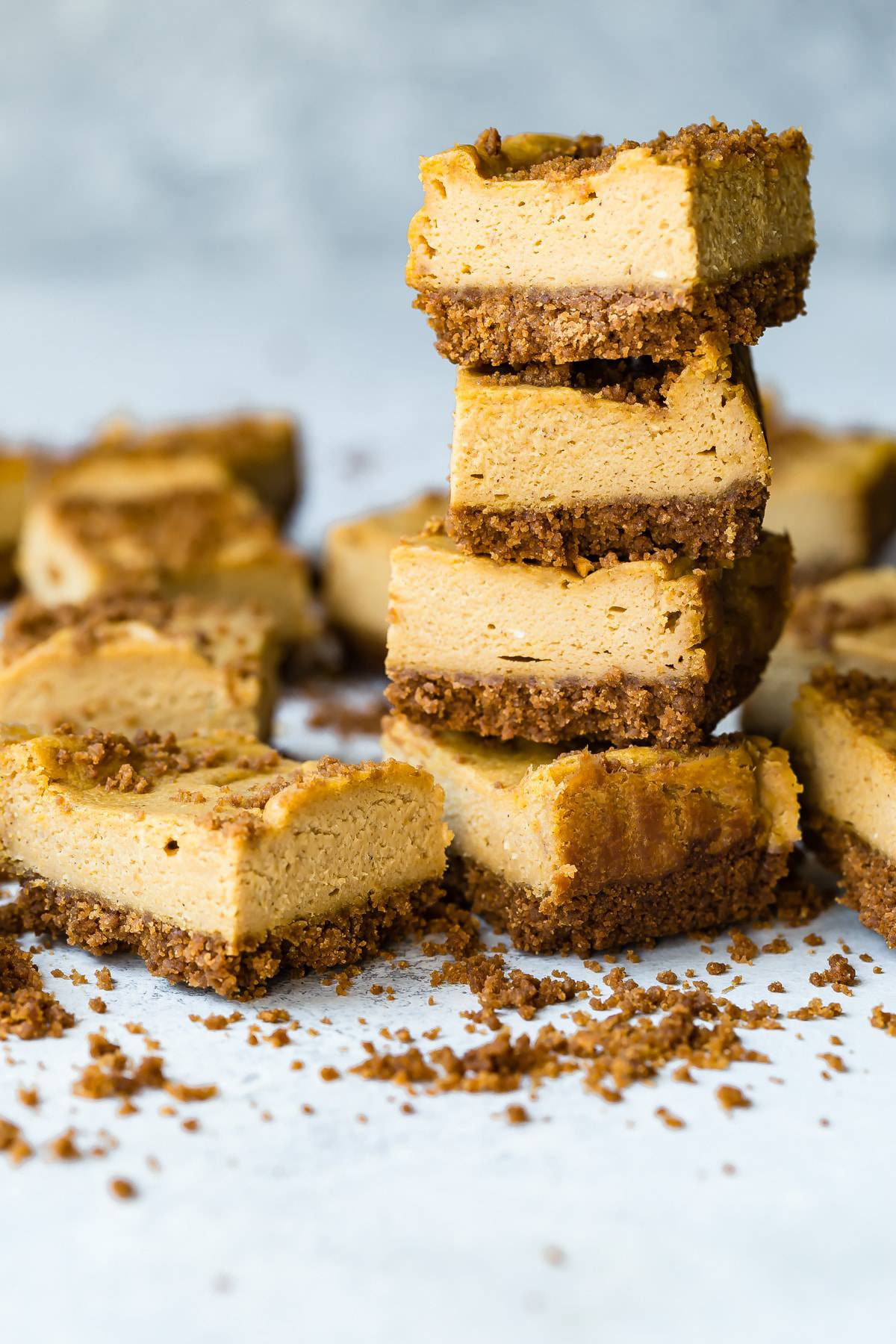 A stack of cookie butter pumpkin cheesecake bars with a crushed speculoos cookie base