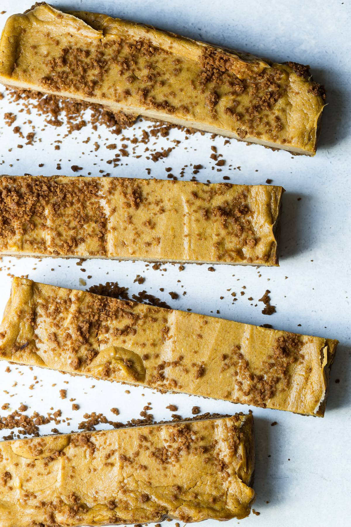 Thick slices of pumpkin cheesecake bars with magical Biscoff cookie butter.