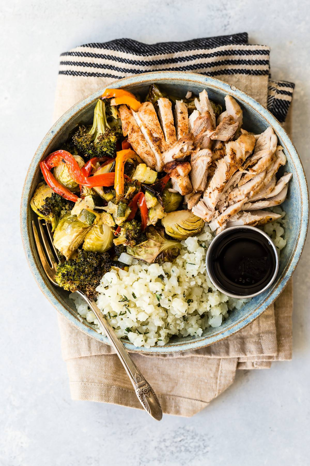 A healthy and delicious low carb chicken bowl loaded with roasted veggies, chicken and cauliflower rice. #lowcarb #paleo #healthyfood #chicken #recipes #cauliflowerrice
