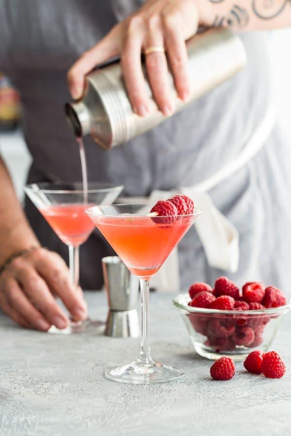 pouring raspberry martini into a glass
