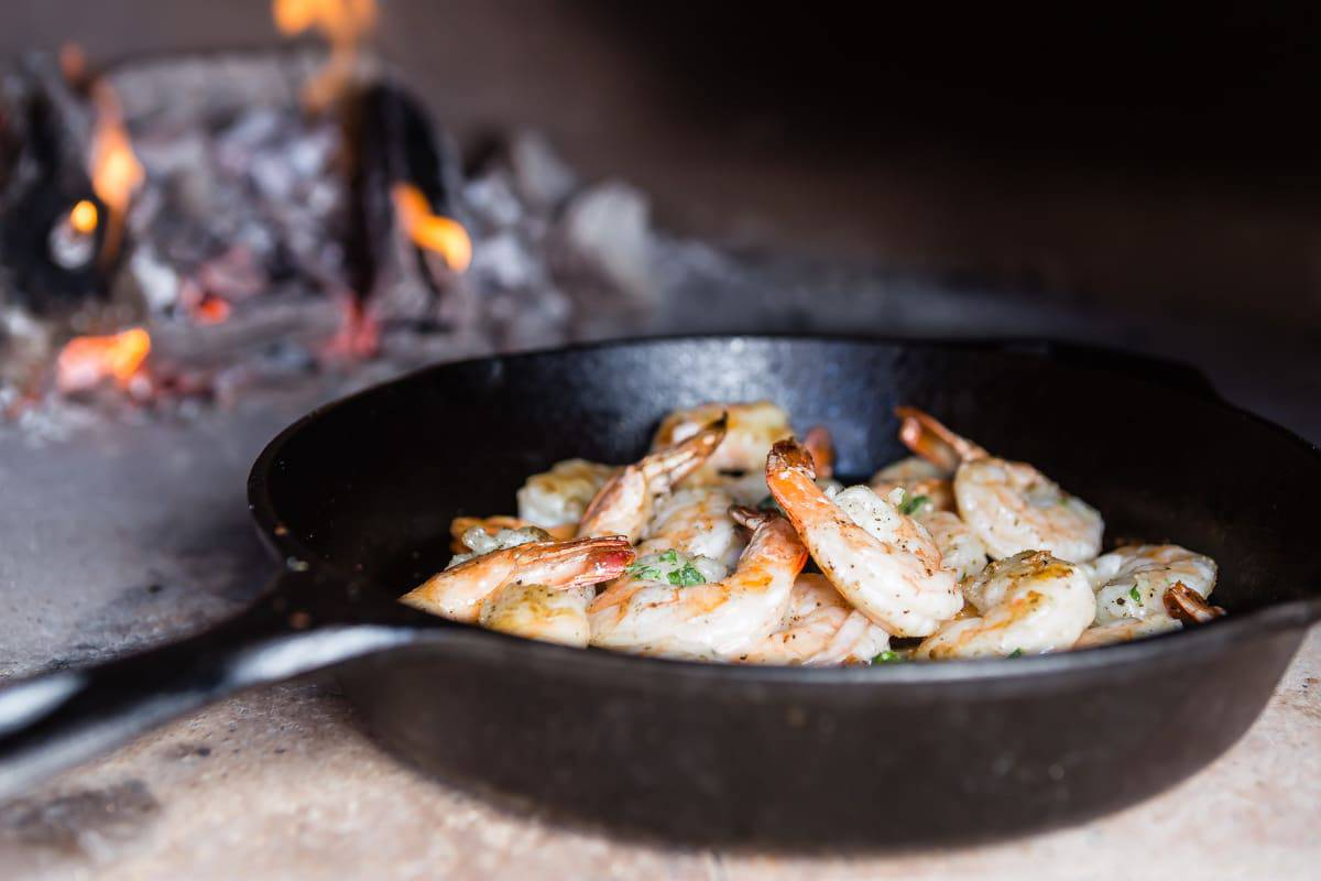 Basil butter shrimp cooking in a wood fired oven