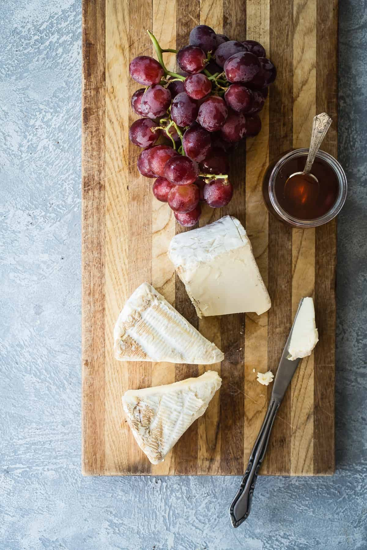 Brie cheese with grapes on a cheese board