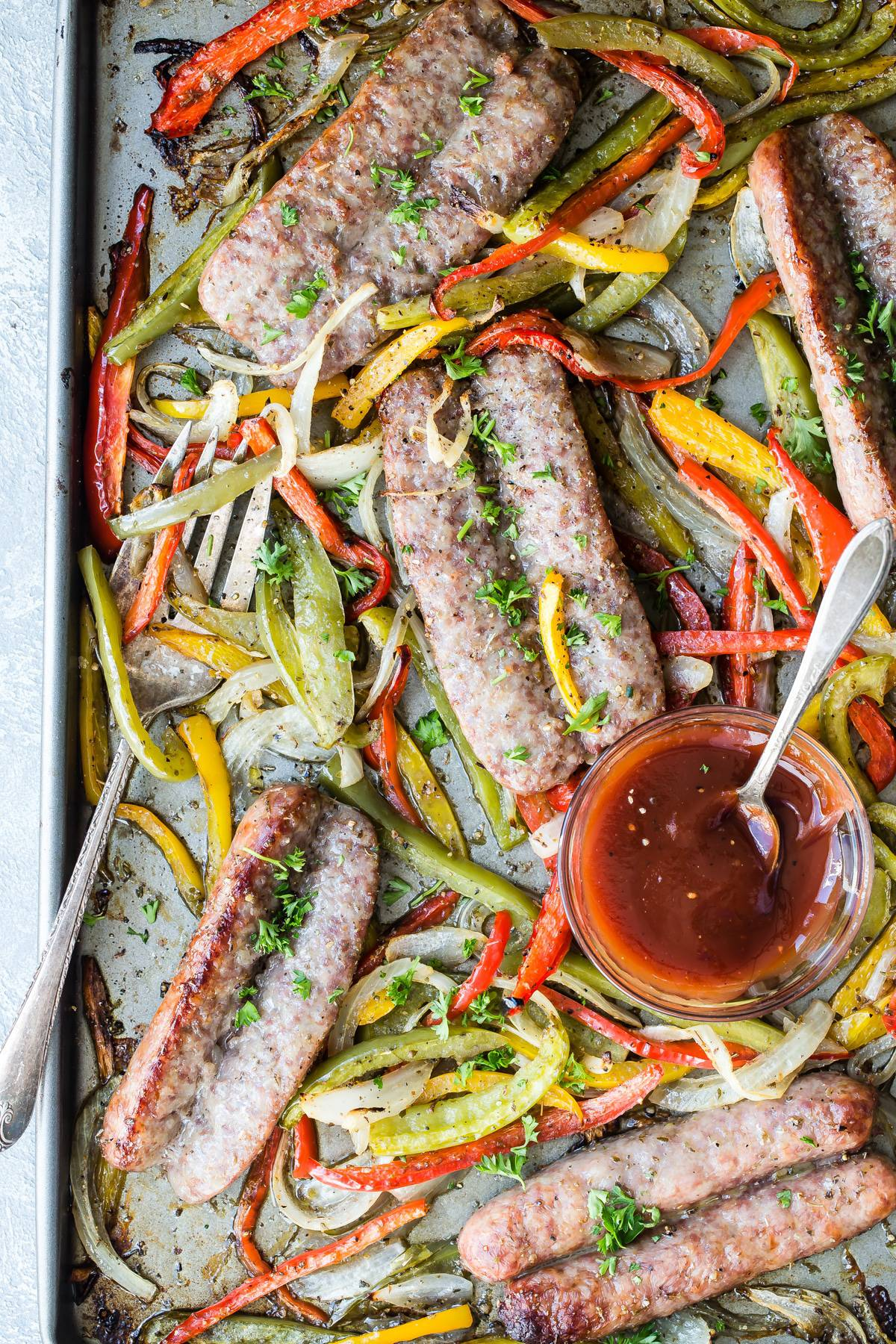 sausage and peppers with onion on a sheet pan