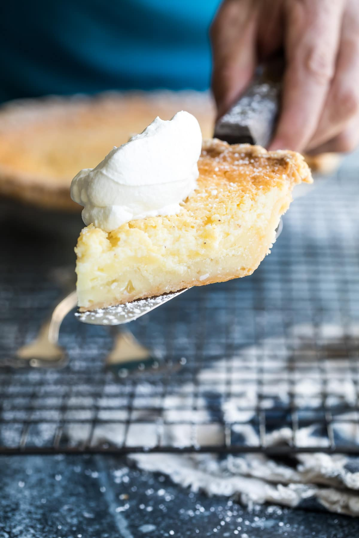 holding a slice of chess pie with a dollop of whipped cream on top of it