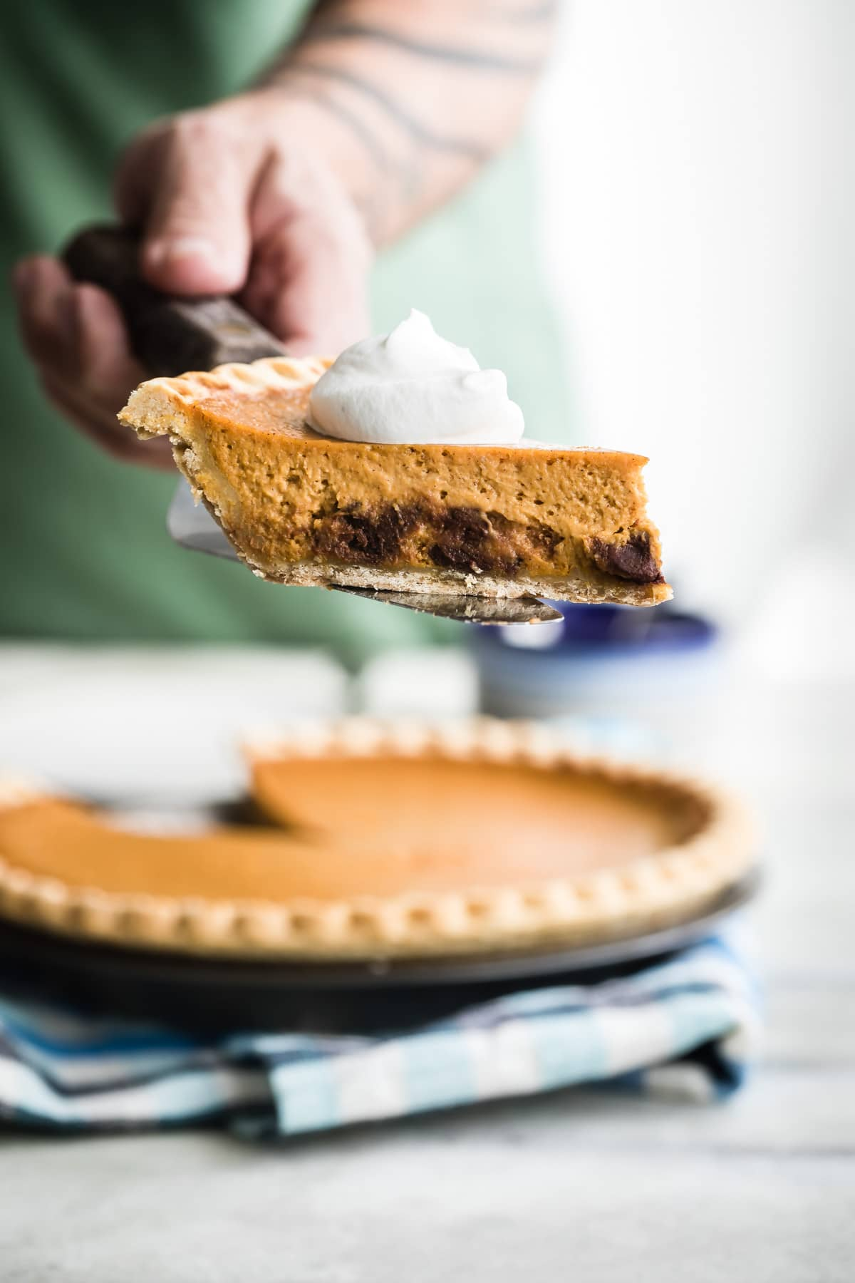 A slice of pumpkin pie with whipped cream on top and chocolate