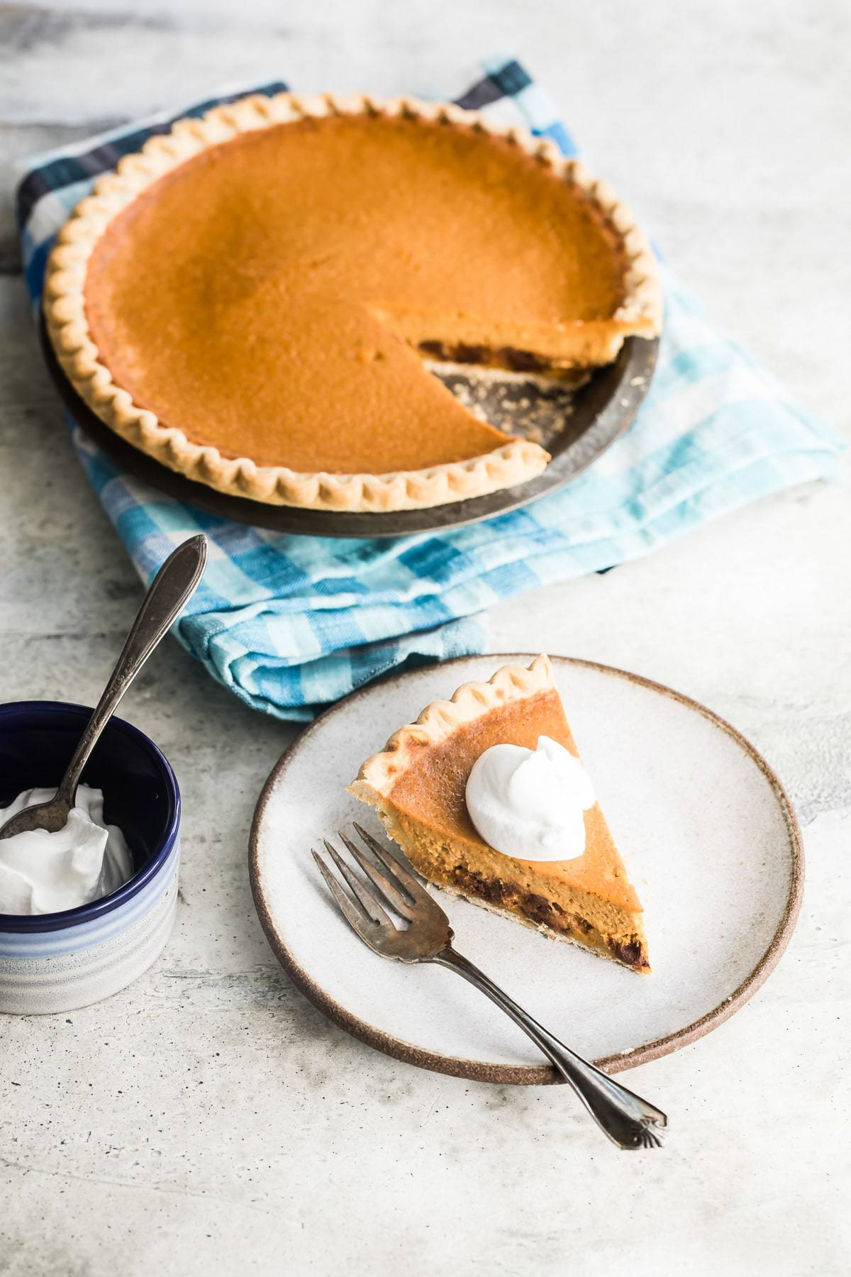 a slice of chocolate pumpkin pie on a plate with a dollop of cream on top