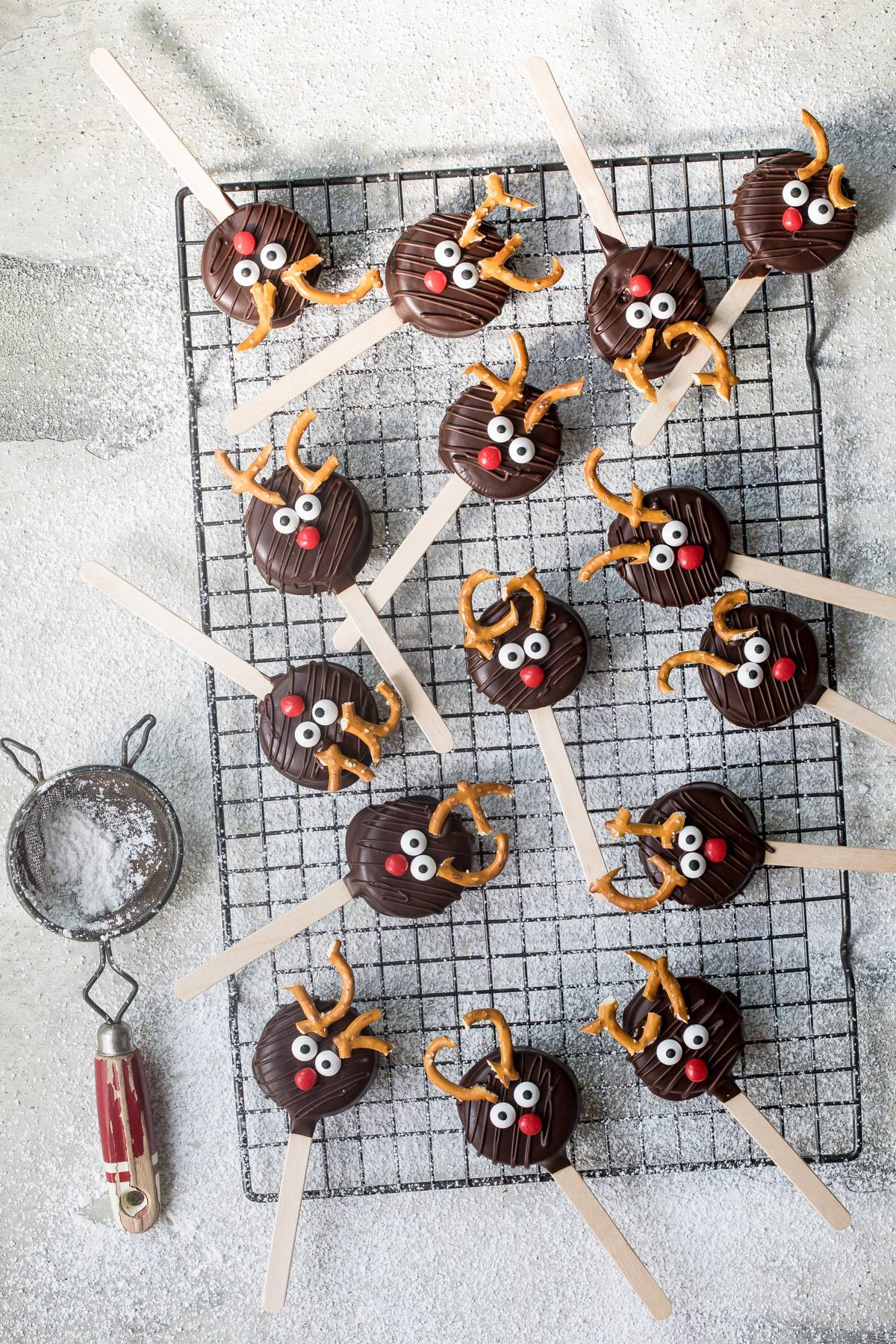 chocolate reindeer cookie pops with powdered sugar