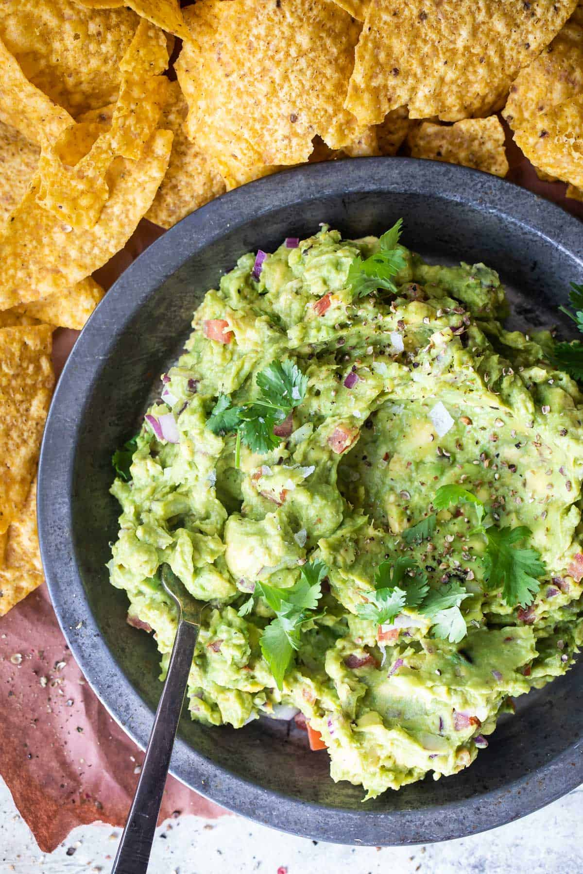 grilled avocado guacamole with cilantro on top and chips
