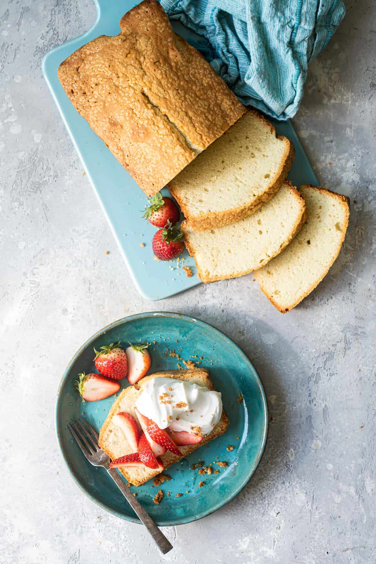 Butter pound cake recipe on a plate with strawberries and cream