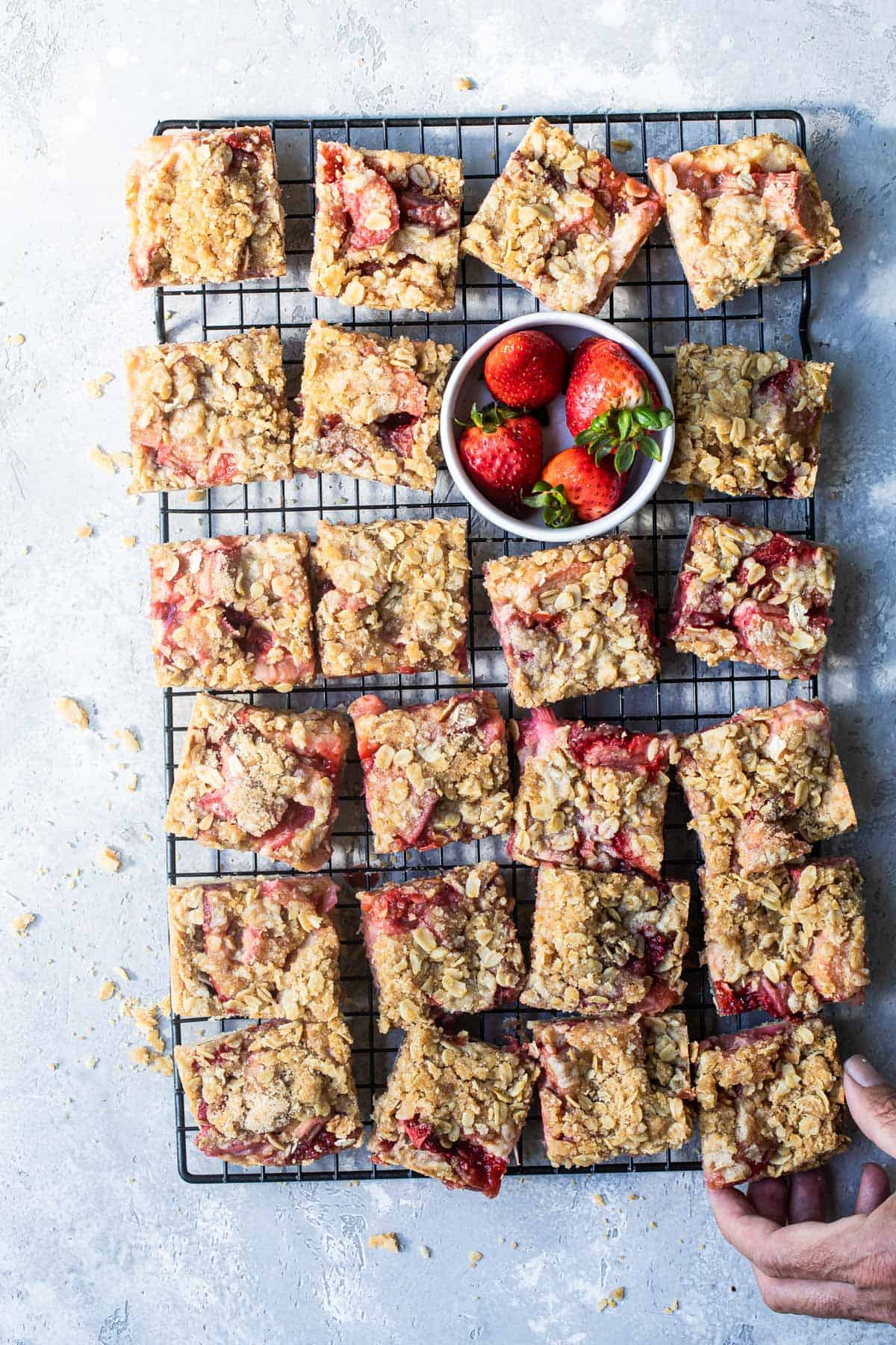Strawberry rhubarb oat bar squares with a bowl of fresh strawberries