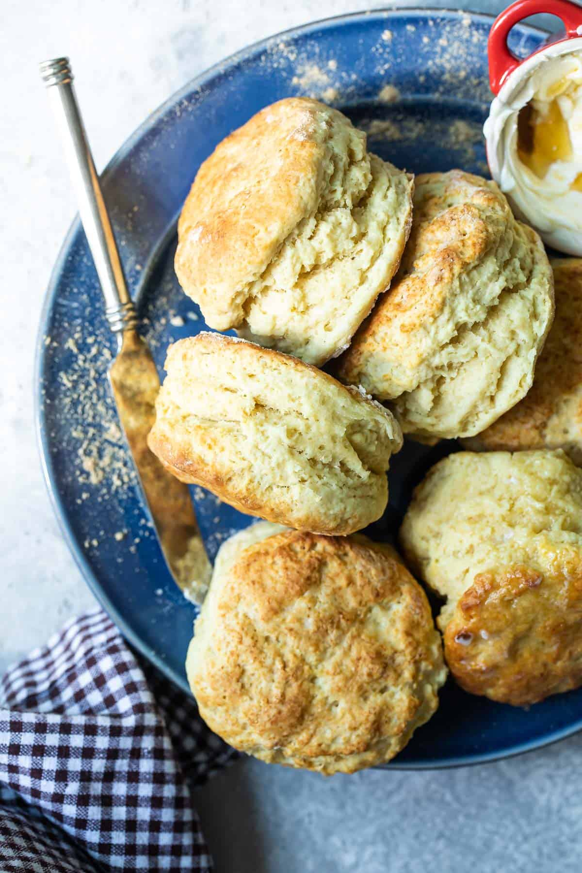 buttermilk biscuits on a plate with honey butter spread