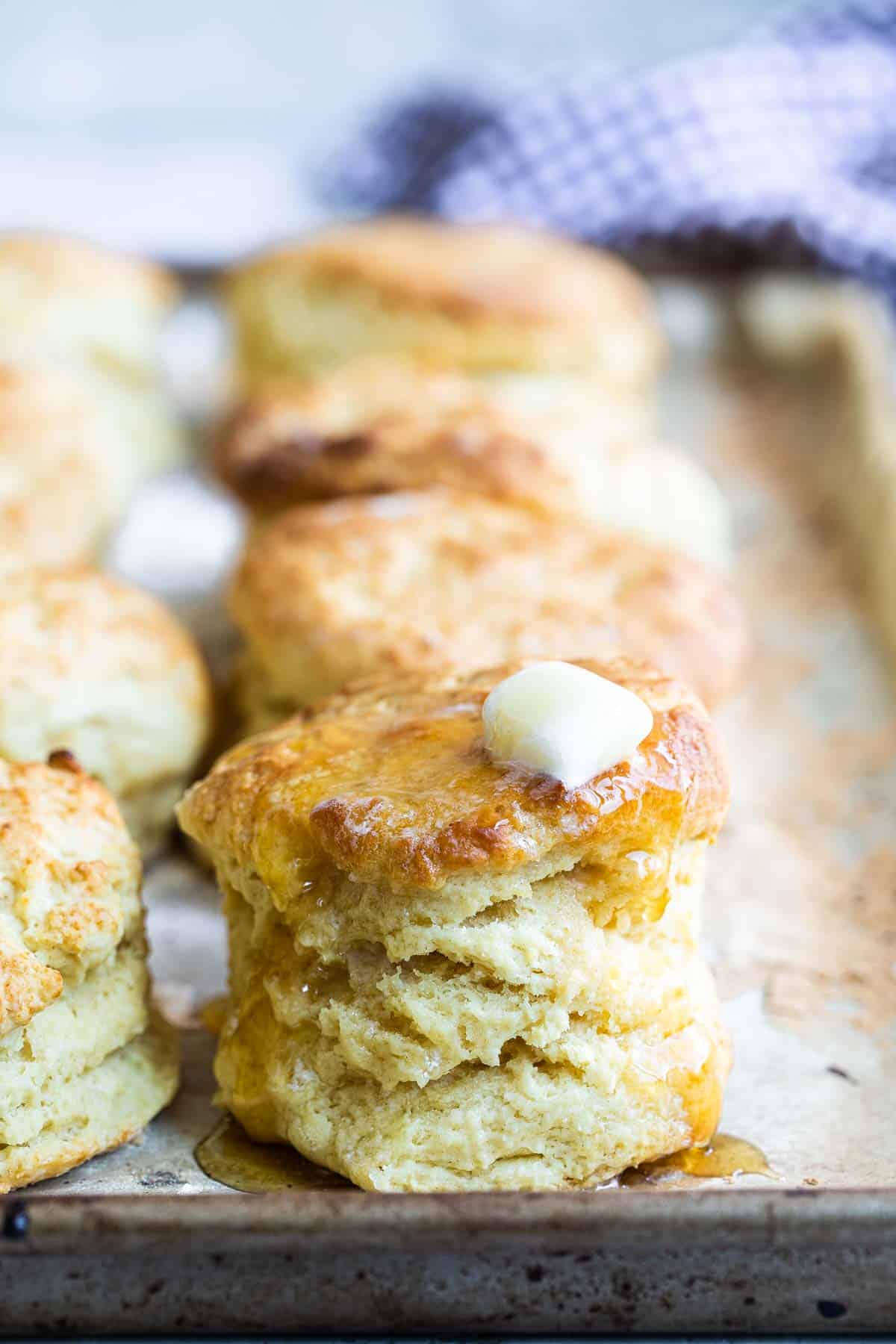 buttermilk biscuits on a pan with butter and honey