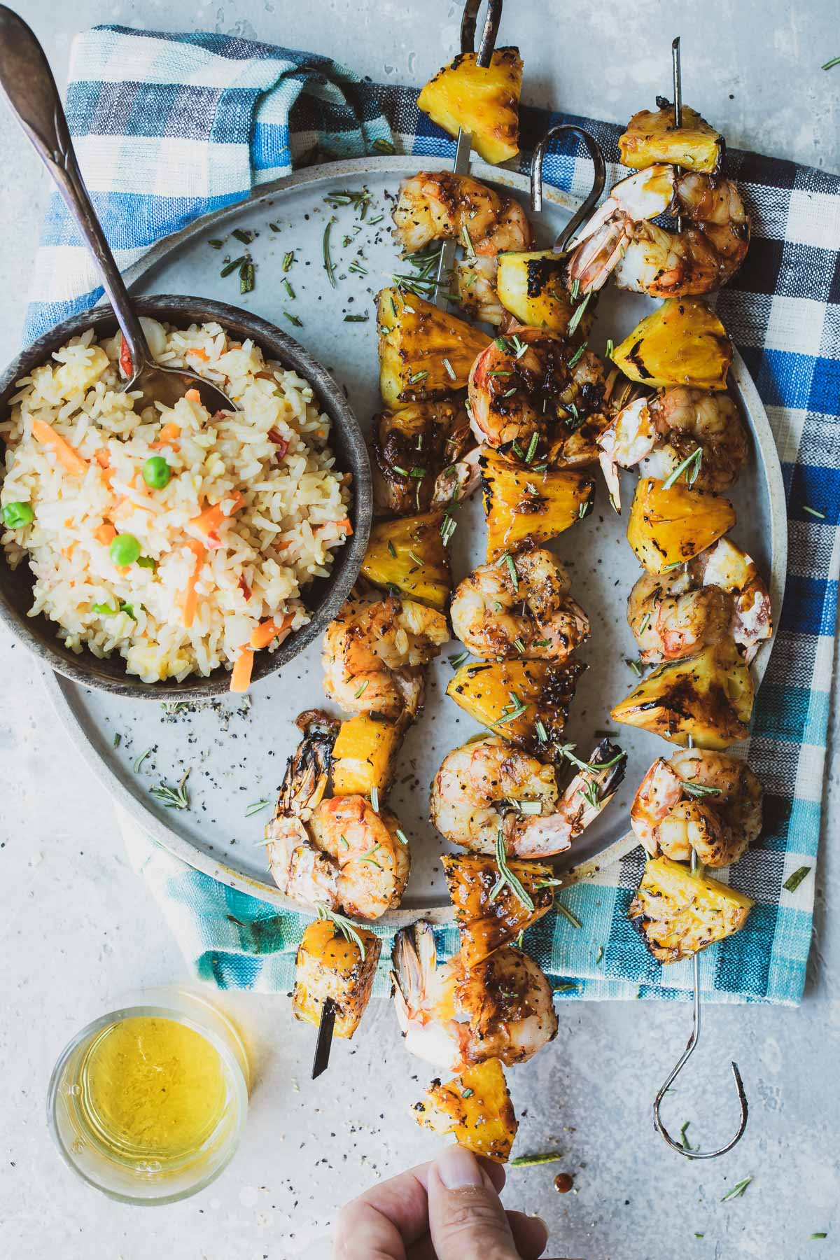 grilled pineapple kebabs on a plate with a side of rice.